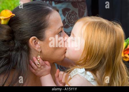 Chiudere orizzontale su ritratto di una madre e figlia giovane (Chief damigella e flowergirl) avente un bacio al Foto Stock