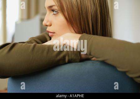 Giovane donna in appoggio sulla parte posteriore della sedia Foto Stock