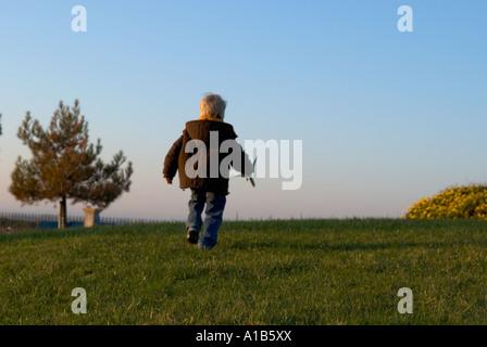 Un piccolo ragazzo di scappare dalla fotocamera con un piano giocattolo in mano Foto Stock