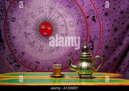 Teiera araba e vetro con Touareg tè sulla pittura zodiacali segno zodiacale sfondo viola Foto Stock