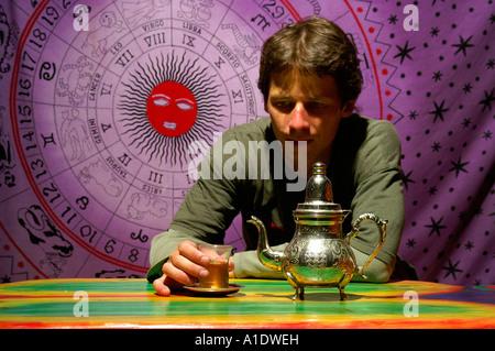Uomo seduto con gli arabi e teiera in vetro con Touareg tè sulla pittura zodiacali segno zodiacale sfondo viola Foto Stock