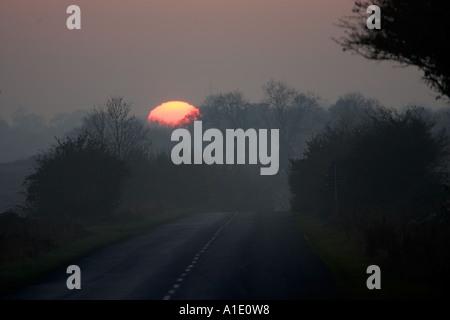 Inverno il sole tramonta su empty country road Swinbrook Oxfordshire UK Foto Stock