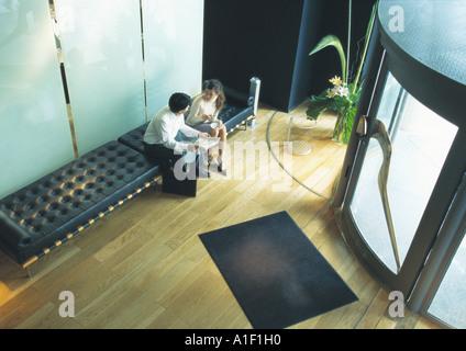 L uomo e la donna seduta sul banco di prova nella lobby, ad alto angolo di visione Foto Stock