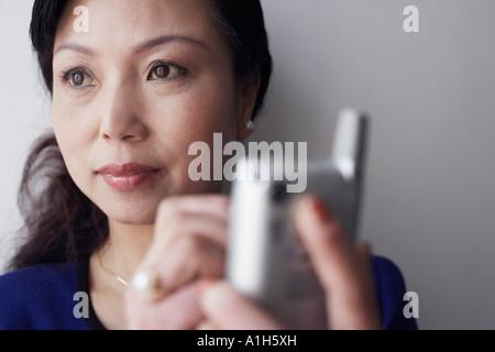 Close-up di una donna matura in possesso di un telefono cellulare di pensare Foto Stock