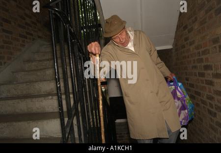 Uomo anziano il trasporto delle borse della spesa in una rampa di scale su un alloggiamento estate in Londra Foto Stock