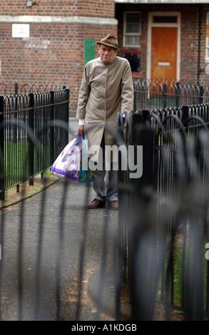 Uomo anziano che trasportano shopping e passeggiate home sul complesso residenziale nella zona est di Londra Foto Stock