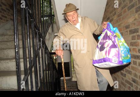 Uomo anziano il trasporto delle borse della spesa in scale su una torre di Londra il blocco Foto Stock