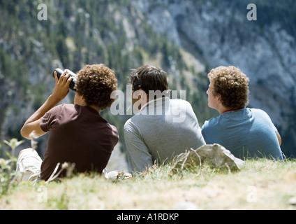 Tre uomini guardando a Mountain View, uno utilizzando il binocolo Foto Stock