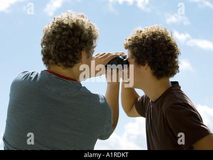 Due uomini con il binocolo, vista posteriore Foto Stock