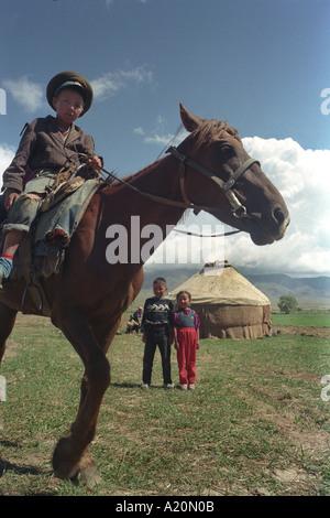 Giovane ragazzo su un cavallo di fronte alle loro famiglie yurt, nei pressi del lago Issyk Kul, Kirghizistan Foto Stock