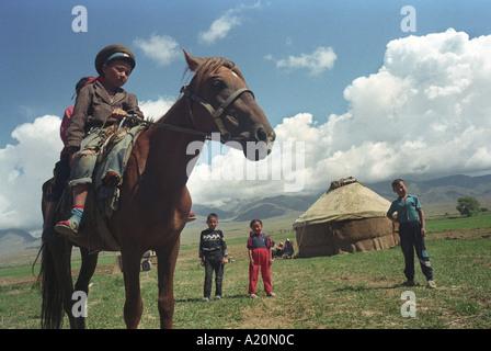 Due bambini su un cavallo di fronte alle loro famiglie yurt, nei pressi del lago Issyk Kul, Kirghizistan Foto Stock
