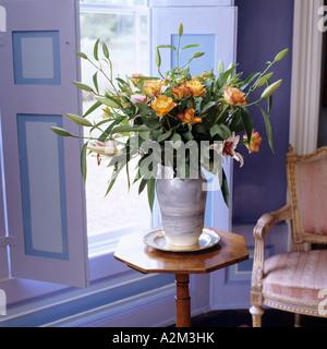 Vaso di fiori sulla pianta ottagonale nella parte anteriore della finestra con otturatori Foto Stock