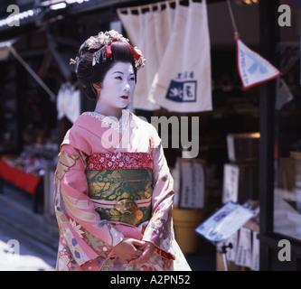 La ragazza di maiko partecipante Geisha costume passeggiando per le strade di Kyoto Gion indossare il kimono obi Foto Stock