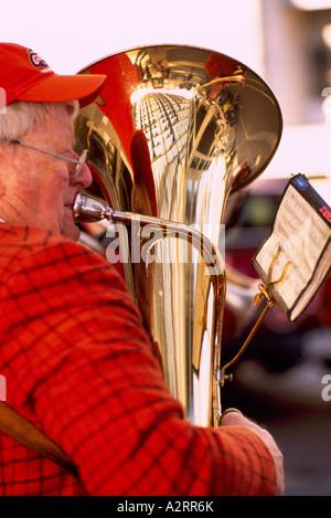 Un anziano uomo giocando una tuba in una band Foto Stock