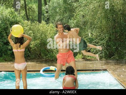 Padre e figli giocare in piscina Foto Stock
