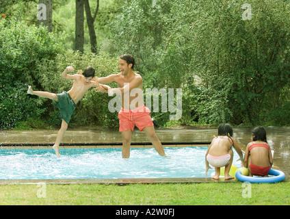 Padre gettando il figlio in piscina Foto Stock