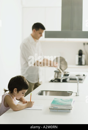 Bambino facendo i compiti sul bancone cucina mentre padre cuochi Foto Stock