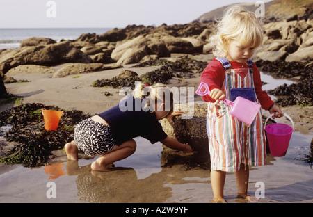 Le ragazze giovani in rock pool insieme su una spiaggia in Cornovaglia nel Regno Unito Foto Stock