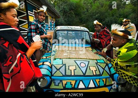 Persone uomini africani carte da gioco intorno ad un vecchio modello di auto rilasciato Villaggio Culturale di Lesedi vicino a Johannesburg in Sud Africa