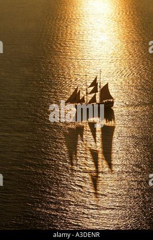 Nave a vela sul mare al tramonto, Oia - Santorini, Grecia Foto Stock