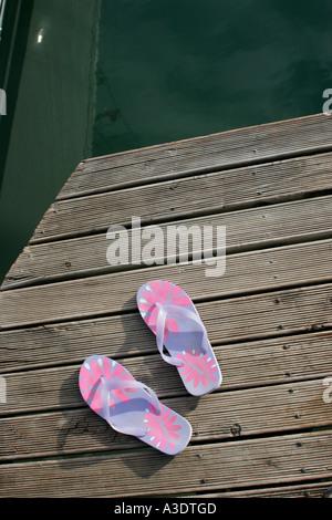Coppia di sandali di plastica con motivo floreale su una banchina in legno su acqua, Isole Figi Foto Stock