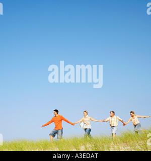 Due coppie mature tenendo le mani e piedi su un paesaggio Foto Stock