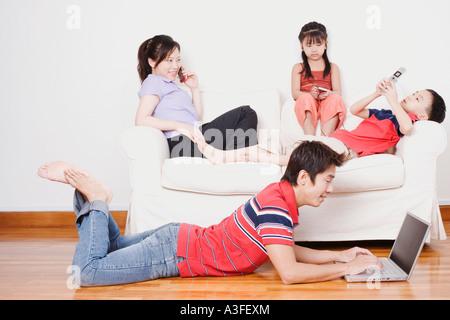 Giovane donna e suo figlio e figlia seduta su un divano con un mid Adulto Uomo sdraiato sul pavimento con un computer Foto Stock