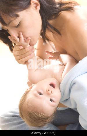 La madre del bambino di baciare la mano Foto Stock