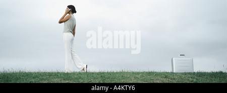 Donna che cammina su erba parlando al cellulare, valigetta metallica sul terreno dietro di lei