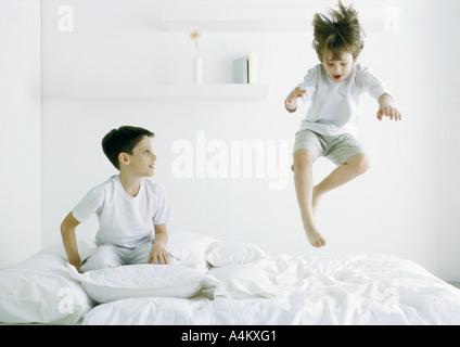 I ragazzi sul letto, uno a metà in aria Foto Stock