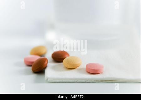 Selezione di pillole davanti a un bicchiere di acqua Foto Stock