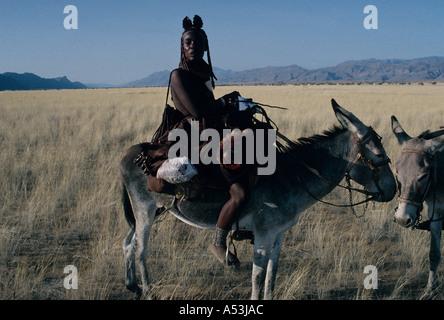Himba donne nomadi nel tradizionale abbigliamento in pelle attraversando il Marienfluss su donkey in Kaokoland Namibia Foto Stock