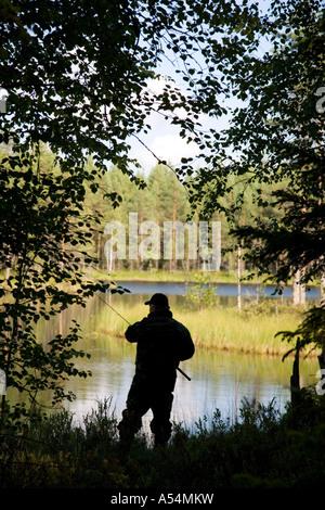 Silhouette di un anziano pescatore di pesca in un piccolo lago di foresta , Finlandia Foto Stock