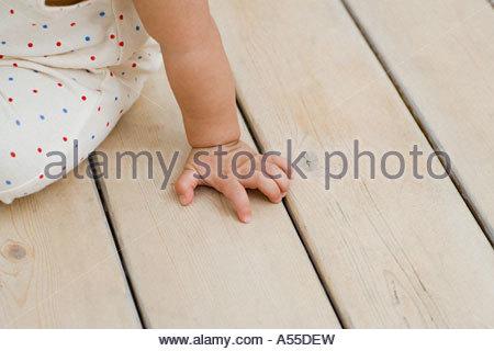 Bambino seduto su un pavimento di legno Foto Stock
