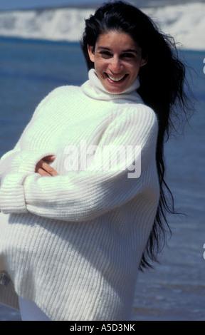3431f10cb936 Ritratto di anglo-asian donna incinta in bianco che scorre vestiti  permanente sulla spiaggia sabbiosa  Ritratto fortemente incinta anglo-donna  asiatica ...