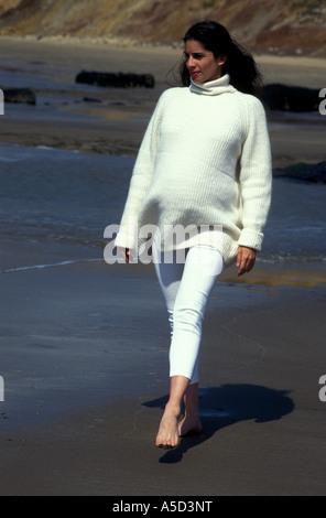 12742a18d93a Anglo-asian donna incinta vestita di bianco a piedi lungo la spiaggia sulla  giornata di