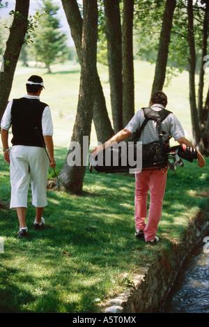 I golfisti in cerca di palla sotto gli alberi, vista posteriore Foto Stock