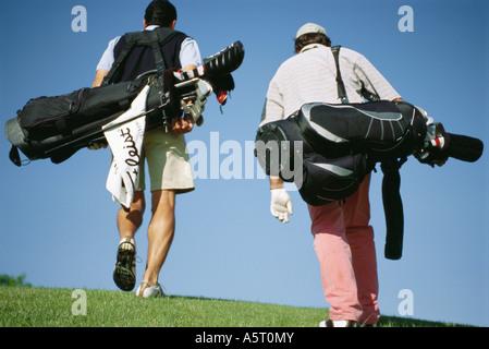 Gli amanti del golf che trasportano le sacche da golf, vista posteriore Foto Stock