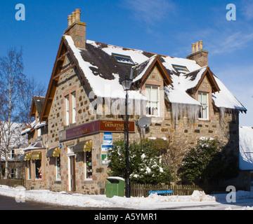 Edifici coperti in Lunghi ghiaccioli pendenti dal tetto della McLeans souvenir shop in inverno, Braemar Royal Deeside Foto Stock