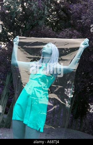 Bella femmina modello tenendo il foglio di plastica sulla faccia che mostra lei è tagliato fuori dal mondo reale Foto Stock