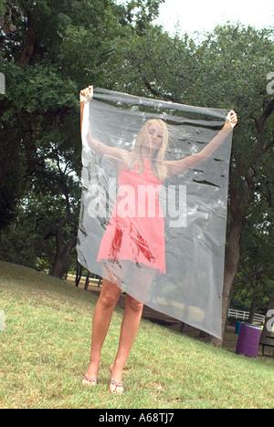 Bella bionda moda azienda modello foglio di plastica tra lei e il mondo reale Foto Stock