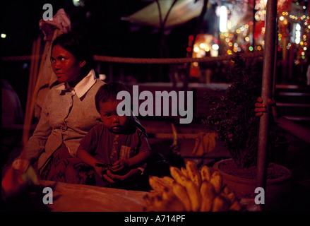 Cambogia Phnom Penh madre e figlio seduti a fornitori di frutta lungo Sisowath Quay da Tonl Sap Fiume sulla serata Foto Stock