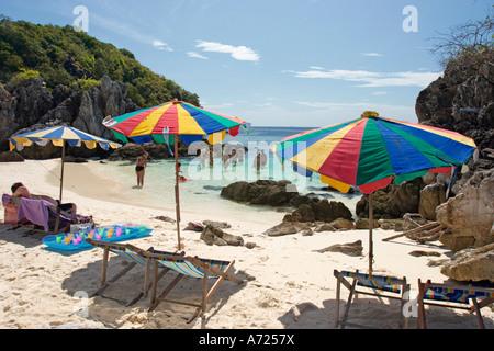 Sedie a sdraio e ombrelloni colorati sulla spiaggia di sabbia bianca. Koh Khai, una piccola isola corallina vicino Foto Stock