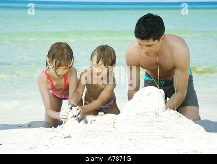 Padre e due bambini che giocano nella sabbia sulla spiaggia Foto Stock