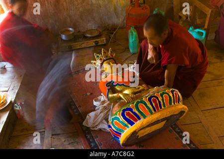 Giovane monaco verniciatura un Buddha all'interno del monastero di Thiksey Ladakh Himalaya indiano
