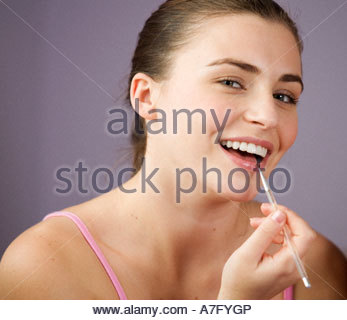 Una ragazza adolescente applicando lip gloss Foto Stock