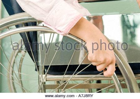 Una donna seduta su una sedia a rotelle Foto Stock