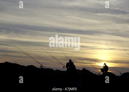 Silhouette di due pescatori al tramonto Foto Stock