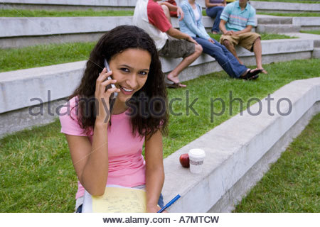 Ragazza adolescente 17 19 seduta vicino amici note di studio in giro usando il telefono cellulare sorridente Foto Stock