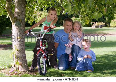 Padre di tre figli 3 9 inginocchiati su erba accanto all albero nel giardino ragazza seduta sulla bici sorridente Foto Stock